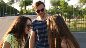 Young handsome bearded guy flirting with two pretty fashionable girls outdoors stock video footage