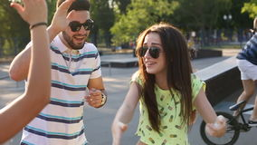 Young handsome bearded guy funny greets two pretty fashionable girls outdoors stock video footage