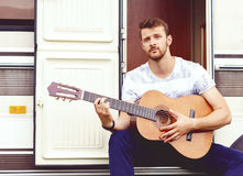 Young and handsome bearded guy playing guitar outdoors. Holiday, Royalty Free Stock Photos