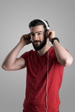 Young handsome bearded guy putting on white headphones Stock Photography