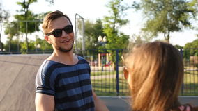 Young handsome bearded guyflirting with two pretty fashionable girls outdoors stock footage