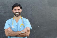 Young handsome bearded health care worker smiling crossing his arms with copy space Royalty Free Stock Photo