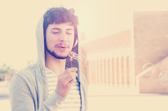 Young handsome bearded hipster man blowing bubbles soap  Royalty Free Stock Photos