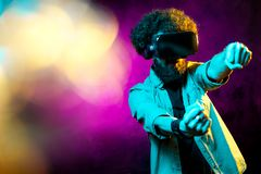 Young handsome bearded hipster man with curly hair driving virtual car with goggles in neon lights. Smartphone using. With VR headset royalty free stock image