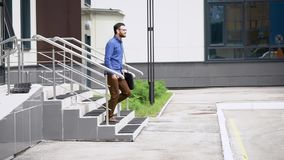 Young handsome bearded man in blue shirt and brown trousers is going outside. Student walking outdoors happily after