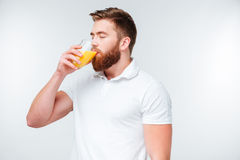 Young handsome bearded man drinking orange juice. On white background Royalty Free Stock Images