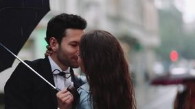 Young handsome bearded man in an elegant costume and tiny attractive woman in casual wear with cornflower bouquet. Young. People running under the umbrella in stock video footage