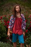 Young handsome bearded man hippie with dreadlocks with his guitar standing on the red roses flower background stock photo