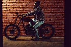 Bearded biker man on motorbike. Young handsome bearded man hipster or biker with long beard near metallized motorbike or motor cycle with wheels on red brick royalty free stock photography