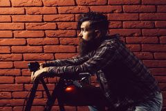Bearded biker man on motorbike. Young handsome bearded man hipster or biker with long beard sitting on metallized motorbike or motor cycle on red brick wall royalty free stock photos