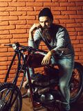 Bearded biker man on motorbike. Young handsome bearded man hipster or biker with long beard sitting on metallized motorbike or motor cycle with wheels on red stock image