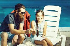Happy small girl and man at swimming pool royalty free stock images