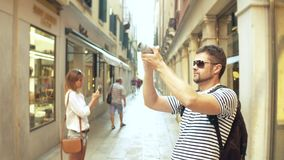 Young handsome bearded man making photos of a narrow street with his camera Stock Photos