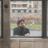 Young handsome bearded man posing behind a glass Stock Image