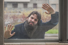 Young handsome bearded man posing behind a glass Royalty Free Stock Photo