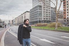 Young handsome bearded man posing in the city streets Royalty Free Stock Photos