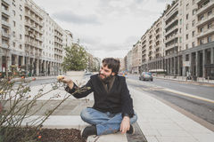 Young handsome bearded man posing in the city streets Royalty Free Stock Photo