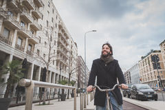 Young handsome bearded man posing with his bicyle Royalty Free Stock Images