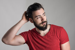 Young handsome bearded man in red t-shirt scratching head looking away. Over gray background Royalty Free Stock Photo