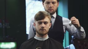 Handsome young man getting a haircut at the barbershop stock image