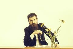 Bearded man professor glasses at table. Young handsome bearded man scientist or professor with long beard and teacher glasses with pencil and book or notepaper stock photography