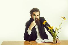 Bearded man professor glasses at table. Young handsome bearded man scientist or professor with long beard and teacher glasses with pencil and book or notepaper stock photos