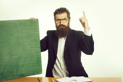 Bearded man professor glasses with blackboard. Young handsome bearded man scientist or professor in teacher glasses with long beard with green blackboard chalk royalty free stock photography