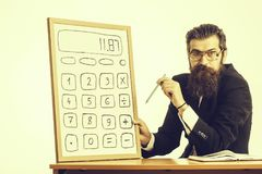 Bearded man professor glasses with calculator. Young handsome bearded man scientist or professor in teacher glasses with long beard holding board with calculator royalty free stock photo