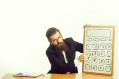 Bearded man professor glasses with calculator. Young handsome bearded man scientist or professor in teacher glasses with long beard holding board with calculator royalty free stock photos