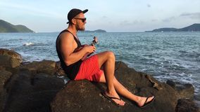 Young handsome bearded man singing and playing ukulele on the beach rocks. HD sunset ocean view. Thailand, Phuket. stock video