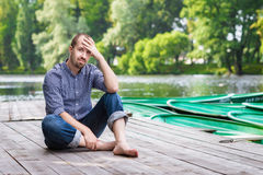 Young handsome bearded man sitting on wooden pier in summer day Royalty Free Stock Photo