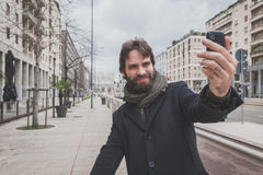 Young handsome bearded man taking a selfie in the city streets Royalty Free Stock Photography