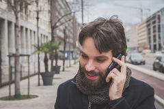 Young handsome bearded man talking on phone Stock Photo