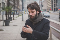 Young handsome bearded man texting in the city streets Royalty Free Stock Photography