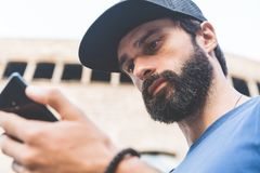 Young handsome bearded man using his smartphone on the street. Blurred background. Horizontal. Young handsome bearded man using his smartphone on the street Royalty Free Stock Photos