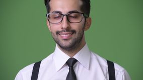 Young handsome bearded Persian businessman against green background