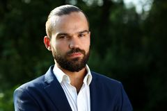 Young handsome bearded serious businessman in blue suit Stock Photo