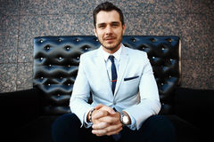 Young handsome bearded stylish man sitting on comfortable leather sofa Stock Photography