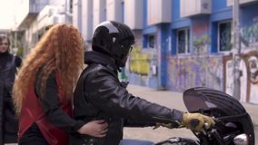 Young handsome biker guy in helmet and attractive funny redhead girl are sitting on a bike in urban graffiti scene stock video footage