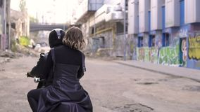 Young handsome biker guy in helmet and attractive girl sre sitting on a bike in urban graffiti scene stock footage