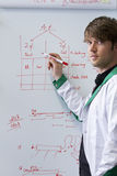 Young handsome biotech student with whiteboard. Young handsome biotech PhD student lecturing in front of whiteboard with formulas on it. The student wears a Stock Photography