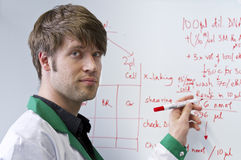 Young handsome biotech student with whiteboard. Young handsome biotech PhD student lecturing in front of whiteboard with formulas on it Stock Photography