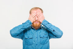 Young handsome blond bearded male with eyes covered by hands Royalty Free Stock Image