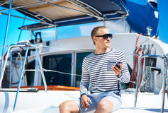 Young and handsome blond man talking on a mobile phone. Young and handsome man on a sailing boat talking on a mobile phone royalty free stock photo
