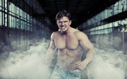 Young and handsome bodybuider in factory Stock Images