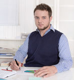 Young handsome bookkeeper working with graphs at desk. Stock Photography