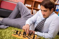 The young handsome boss playing chess during break. Young handsome boss playing chess during break stock photos