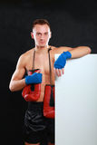 Young handsome boxer man standing near board , isolated on black background Royalty Free Stock Photos