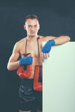 Young handsome boxer man standing near board , isolated on black background Royalty Free Stock Photo