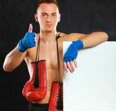 Young handsome boxer man standing near board and showing ok,  on black background Royalty Free Stock Photos